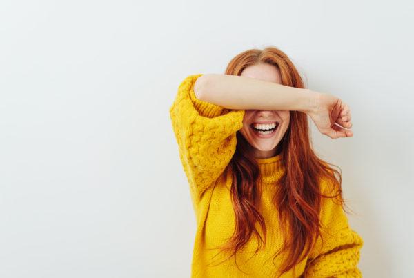 rothaarige frau versteckt sich lachend hinter ihrem arm