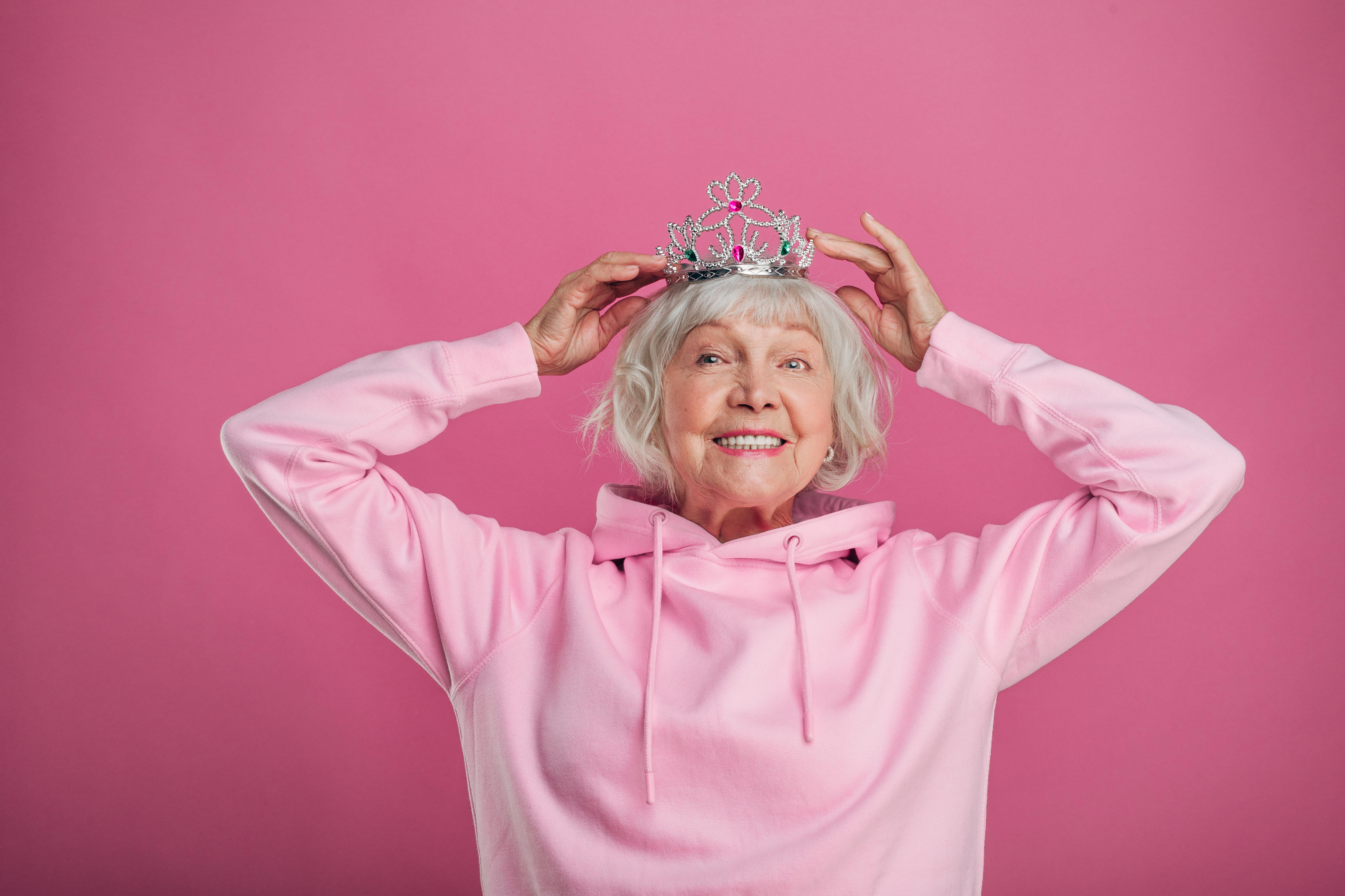 ältere Dame in rosa Pullover und Krone auf dem Kopf